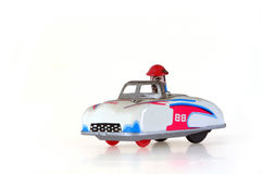 Tin Toy Racing Car. Retro tin toy clockwork racing car, with driver. Isolated on white background stock image