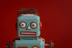Tin toy robot against red background Stock Photo