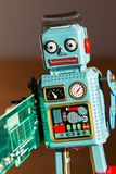 Tin toy robot carries computer circuit board, artificial intelligence concept Royalty Free Stock Photo