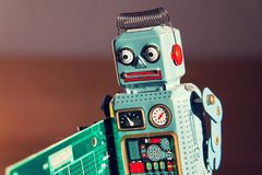 Tin toy robot carries computer circuit board, artificial intelligence concept Royalty Free Stock Photography