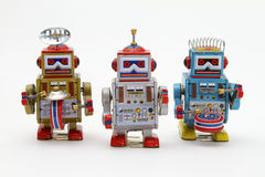 Tin Toy Robots. A marching band of 3 tin toy robots in gold, silver and blue Stock Images