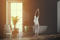 Tina blanca en un cuarto de baño negro, butaca, mujer Imagen de archivo libre de regalías
