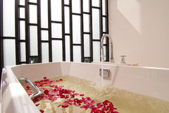 Tina de baño con agua y las flores Fotos de archivo