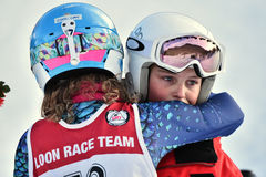 Tina Sutton Memorial. Unidentified participant calming down girl who felt down during junior ski race Stock Photos