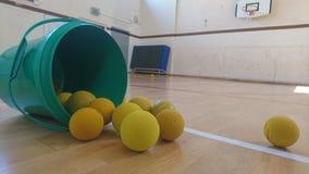 Tina verde de pelotas de tenis de los gorrones en el piso del sportshall Fotos de archivo