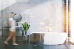 Tina y fregadero blancos en un cuarto de baño del ático, mujer Foto de archivo