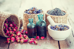 Tincture, basket with rose buds, lavender and dried flowers in mortar Stock Image