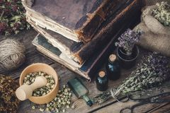 Tincture bottles, assortment of dry healthy herbs, old books, mo. Rtar, scissors on old wooden desk. Herbal medicine. Top view stock photo