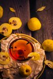 Tincture cup fruit quince wooden table Stock Photography