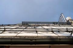 Tindak waarop de sneeuw, de zichtbare voorgevel van het gebouw, de goot, de ventilatieschoorstenen en anti-sneeuwsysteem ligt royalty-vrije stock afbeelding