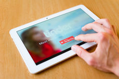 Tinder. Man's hand use with his fingers tablet. Tinder app is on the screen. Tinder is popular social network for meeting new people and sexual partners royalty free stock photos