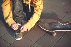 Tinejder avant de faire de la planche à roulettes attache des dentelles sur des espadrilles Photo libre de droits