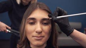 Tingidura da sobrancelha O mestre pinta as sobrancelhas com hena a uma menina bonita, pinta com uma escova no sal?o de beleza da vídeos de arquivo