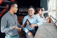 Tinido de riso dos amigos com garrafas de cerveja Foto de Stock