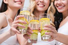 Tinido de sorriso das mulheres com vidros da água com limão Imagem de Stock Royalty Free