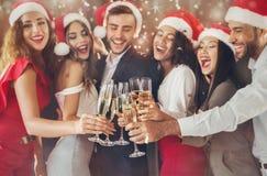 Tinido diverso dos amigos com vidros do champanhe na véspera do ` s do ano novo fotos de stock