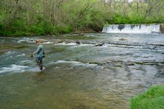 Tinker Creek Dam and a Trout Fisherman. Roanoke, Virginia, April 18th: A trout fisherman on Tinker Creek with Tinker Creek Dam in the background located in the Royalty Free Stock Images