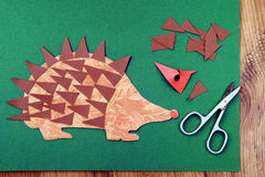 Tinker a hedgehog with paper and scissors.  Stock Images