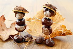 Tinker little chestnut figures auf nuts and leaves.  Royalty Free Stock Photo