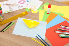 Tinker with paper. Colorful paper lying on a table to fold of objects, in the background of children painted pictures Stock Images