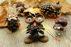 Tinker small owl, squirrel figure,snail and ladybug made of pine. Cone and acorn parts. glue and tooth sticks aside Stock Photo