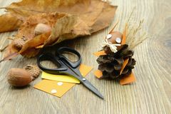 Tinker small squirrel figure made of pine cone and paper. acorn. Leave scissors and paper aside Stock Images