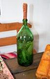 Tinktur av pepparrot och persilja på utopier En flaska av likör pluggade majskolvar Arkivfoto