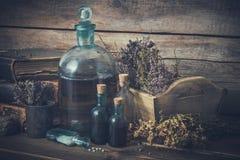 Tinkturflaschen, Phiole Homöopathiekügelchen, alte Bücher, trockene gesunde Kräuter und heilende Drogen lizenzfreie stockfotos