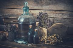 Tinkturflaskor, liten medicinflaska av homeopatismå kulor, gamla böcker, torra sunda örter och läkande droger royaltyfria foton