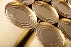 Tinned food. Row of metal cans with no label. Row of the closed metal cans of yellow colour. Diagonal top view Stock Images