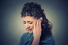 Tinnitus. Closeup sick female having ear pain touching painful head Royalty Free Stock Photo