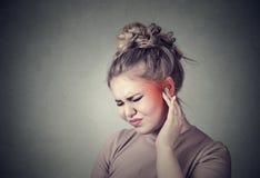 tinnitus Closeupen upp sjukt kvinnligt ha örat smärtar att trycka på hennes smärtsamma huvud som färgas i rött royaltyfri foto
