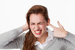 Tinnitus concept, 20s woman teeth grinding for noise or tinnitus problems. Tinnitus concept - enraged young woman having painful headache,covering closed ears Stock Images