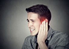 tinnitus Den sjuka mannen som har örat, smärtar att trycka på hans smärtsamma huvud royaltyfri bild