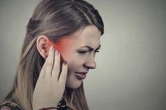 tinnitus Den sjuka unga kvinnan som har örat, smärtar royaltyfri fotografi