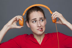 Tinnitus headphones concept for dubious 20s girl. Tinnitus headphones concept - dubious 20s girl listening to loud music with earphones on,removing her earphones Stock Images