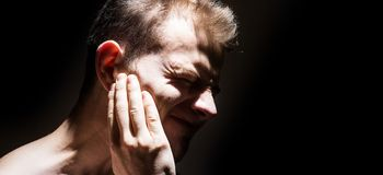 Tinnitus, man on a black background isolated holding a sick ear, suffering from pain royalty free stock photography