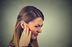Tinnitus. sick young woman having ear pain touching her painful head Stock Images