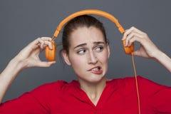 Tinnituskopfhörerkonzept für zweifelhaftes Mädchen 20s Stockbilder