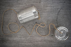 Tins telephone. With rope connecting shaped the word love on wooden background royalty free stock photography
