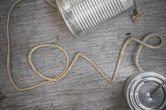 Tins telephone. With rope connecting shaped the word love on wooden background royalty free stock photo