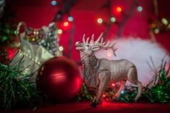 Tinsel γιρλαντών σφαιρών Χριστουγέννων παιχνιδιών αλκών θαμπάδα σε ένα κόκκινο υπόβαθρο στοκ εικόνα με δικαίωμα ελεύθερης χρήσης