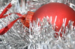 Tinsel and bauble. A red glass bauble in silver tinsel Royalty Free Stock Photos