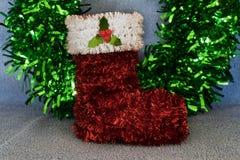 Tinsel Christmas-Strumpfverzierung mit einem grünen Lamettahintergrund Stockbild