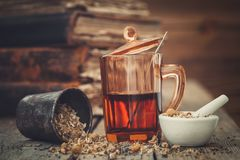 Tint of gezonde thee in glas, mortieren van gezonde madeliefjekruiden stock foto's