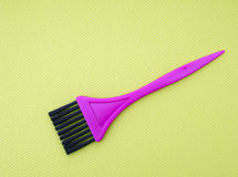 Tint, hair color dye application brush. Pink on bright green fab Royalty Free Stock Image