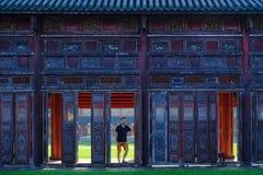 Tint/Vietnam, 17/11/2017: Mens die zich naast sierdeuren in een traditionele pavillion in de Citadel complex in Tint bevinden, royalty-vrije stock foto