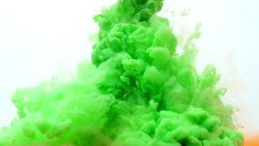 Tinta acrílica verde e alaranjada na água no fundo branco abstraia o fundo video estoque