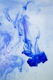 Tinta azul borrosa en agua Imagen de archivo