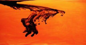 Tinta negra en agua anaranjada Foto de archivo libre de regalías